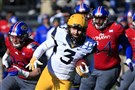 West Virginia quarterback Skyler Howard runs past Kansas linebacker Joe Dineen Jr., left, and defensive tackle Jacky Dezir while on a 42-yard run during the first half.