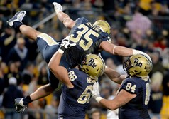 Pitt's Mike Herndon and Connor Dintino lift George Aston after scoring a touchdown against the Louisville Cardinals in the second quarter Saturday at Heinz Field. Pitt defeated the Cardinals, 45-34.