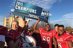 Duquesne players celebrate their 30-20 win against Saint Francis, Pa., Saturday at Rooney Field to clinch the Northeast Conference crown and a playoff berth.