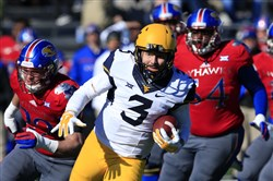 West Virginia quarterback Skyler Howard runs past Kansas defenders while on a 42-yard run during the first half of a game in Lawrence, Kan., Saturday, Nov. 21, 2015.