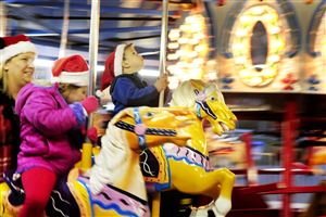 Lorrie Jansen of Wexford rides the carousel with her daughter Francesca, 4, and nephew, Vincenzo, 3 at the CBS Pittsburgh and Duquesne Light 17th annual Santa Spectacular at Point State Park on Light Up Night.