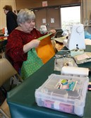 Newlonsburg Church sewer Diane Guthrie pins fabric for a backpack to be sent to the La Croix New Testament Mission in Haiti.