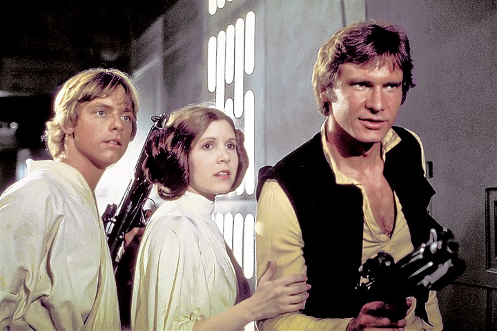 "StylebookSnapshot1129_StarWArs Luke Skywalker (Mark Hamill), Princess Leia (Carrie Fisher) and Han Solo (Harrison Ford) in a production photo from the set of ""Star Wars."""