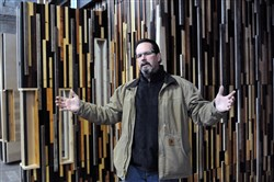 Steve Shelton from the Trade Institute of Pittsburgh stands in front of paneling of reused woods built by his students.