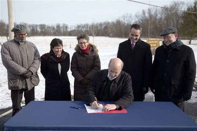 Gov. Tom Wolf signs an executive order restoring a moratorium on new drilling leases involving public lands, Thursday, Jan. 29, 2015, at the Benjamin Rush State Park in Philadelphia. T