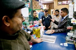 City Council member Saad Almasmari, 28, far right, talks with community members inside a grocery store.