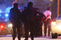 Police lead the suspected gunman away in handcuffs outside a Planned Parenthood facility after a standoff on Friday in Colorado Springs, Colo.