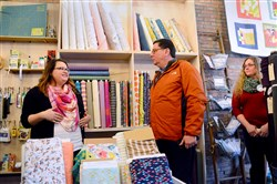 Pittsburgh Mayor Bill Peduto chats Saturday with Michelle Lancet, left, co-owner of Spool Fabric Shop at her store in Allentown.