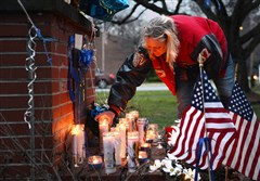 Robin Dubics of New Florence places a candle at a memorial Sunday on Ligonier Street for St. Clair police Officer Lloyd Reed.