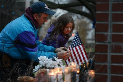 New Florence volunteer firefighter and rescue caption Bernard Sapp helps his daughter Brooke, 5, place a candle at a memorial for St. Clair police officer Lloyd Reed on Sunday night.