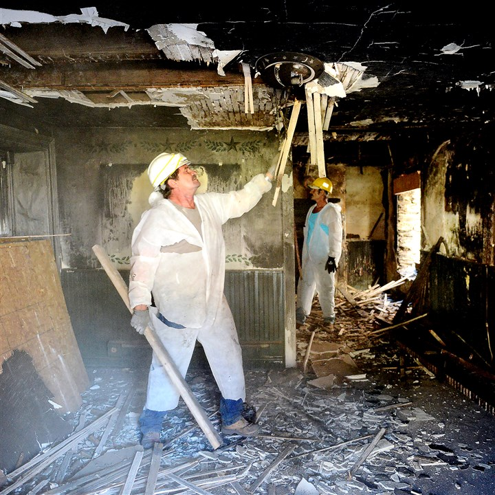 20151104radHarpersFerryLocal01 Randy Custer of Dulyea Construction removes debris from a fire-damaged business in Harpers Ferry, W.Va.