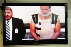 The Colorado Springs shooting suspect, Robert Lewis Dear, right (with public defender Dan King), appears via video for a court appearance Monday.