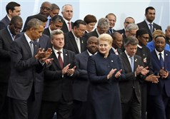 President Barack Obama, left, and Brazil's President Dilma Rousseff, front row third from right, applaud as they pose with world leaders for a group photo at the COP21, United Nations Climate Change Conference, in Le Bourget, outside Paris, today.