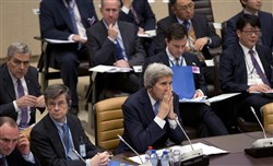 Secretary of State John Kerry, center, waits for the start of a round table meeting of Resolute Support at NATO headquarters in Brussels on Tuesday.
