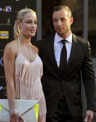 In this Nov. 4, 2012 file photo, South African Olympic athlete Oscar Pistorius and his girlfriend, model Reeva Steenkamp, arrive for an awards ceremony in Johannesburg. The South African court of appeal today convicted Pistorius of murder, overturning a lower court's conviction of the double-amputee Olympian on the lesser charge of manslaughter for shooting his girlfriend to death in 2013.