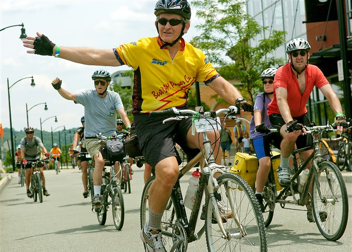 OlderCyclists1213 Mike Magnan of Mesa, Az. waves to other bikers as he rolls into the South Side to complete the Greenway Sojourn bike trek on Saturday, June 30, 2007. Around 500 cyclists spent eight days riding the 335 miles from Washington, DC to Pittsburgh along the nearly completed Great Allegheny Passage.