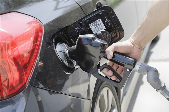 Gas station attendant Carlos Macar pumps gas in Andover, Mass.
