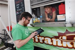 Dave White completes his order with one of Franktuary's owners, Megan Lindsay, at the Franktuary truck.