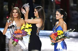 Former Miss Universe Paulina Vega, center, removes the crown from Miss Colombia Ariadna Gutierrez, left, before giving it to Miss Philippines Pia Alonzo Wurtzbach, right, at the Miss Universe pageant on Sunday in Las Vegas. Miss Gutierrez was incorrectly named the winner before Miss Wurtzbach was given the Miss Universe crown.