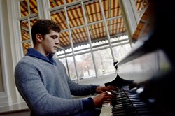 Nationally ranked Pitt wrestler Dom Forys, a North Allegheny grad, plays a song on the piano Wednesday at the Pitt Student Union.