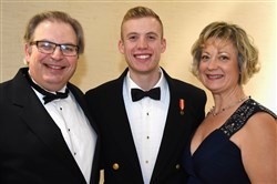 Chairperson Barbara Foster (right) with her husband Mark, and son Brett, a midshipman at  the U.S. Coast Guard Academy.