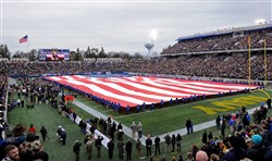 A large American flag is unfurled during the national anthem before the start of the Military Bowl at Navy-Marine Corps Memorial Stadium in Annapolis, Md.