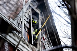 A firefighter works on the last of a fire at a home on Ross Avenue in Wilkinsburg. Seven Pittsburgh firefighters suffered injuries, including burns and broken bones, after rescuing an 86-year-old woman.