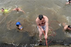 "Tim Sippey, 41, of Elizabeth, climbs out of the Monongahela River after taking the Polar Bear Plunge at 9:30 a.m. on New Year's Day. Mr. Sippey said it was his fifth year participating in the plunge. ""This is the best way to kick off the new year,"" he said."