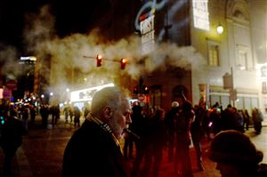 Jim Denny of Mt. Lebanon smokes his daily cigar while standing with his wife Mary Lu Denny, at right, during First Night Pittsburgh, the annual New Year's Eve celebration, in Downtown Pittsburgh on Thursday, Dec. 31, 2015.