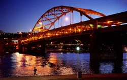 During the twilight hour, a jogger runs Monday along the Three Rivers Heritage Trail past the Fort Duquesne Bridge on the North Shore.