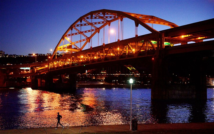 20160104MWHjoggerLocal01 During the twilight hour, a jogger runs Monday along the Three Rivers Heritage Trail past the Fort Duquesne Bridge on the North Shore.
