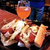 "The ""Kolbassi"" sandwich with melted Jarlsberg cheese and sweet sauerkraut at the Insurrection AleWorks in Heidelberg and a snifter of the house Suppression #2 Double IPA."