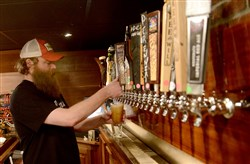 Joel Hollies, a bartender for Caliente Pizza and Draft House, pours a beer at its Railsplitter Speakeasy in Bloomfield.