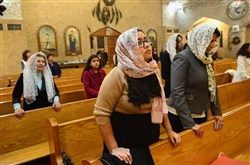 Mary Saieed, 16, and her mother, Erene Saieed, of Moon, say vespers during Christmas Eve service at St. Mary's Coptic Orthodox Church in Ambridge.