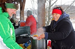 A visitor receives a steaming bowl of chili from a volunteer at the 2015 Winterfest at Moraine State Park.