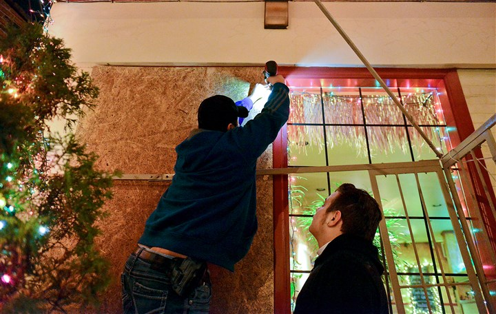 20150108ppCasaRastaWindow2LOCAL Workers board up one of the front windows of Casa Rasta in Beechview, which was broken when someone threw a rock through it Thursday night