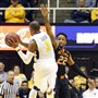 West Virginia's Jevon Carter passes off in the face of Oklahoma State defender Jeff Newberry Saturday in Morgantown, W.Va. Carter led the Mountaineers with 16 points.