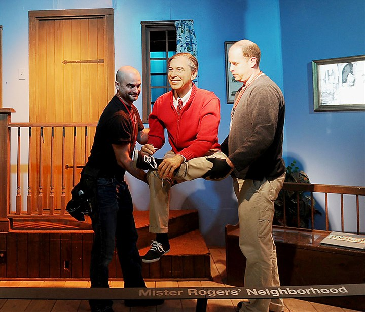 "20150122ng_rogers2-1 Brad Burmeister, left, and Craig Britcher place a likeness of Fred Rogers on a recreation of the TV set of ""Mister Rogers' Neighborhood"" at the Sen. John Heinz History Center last January."