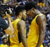 West Virginia's Tarik Phillip (12) and Devin Williams put their heads together as they contemplate their upset of top-ranked Kansas Tuesday night in Morgantown, W.Va.