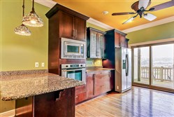 The kitchen has a mixture of closed and glass-front cabinets, quartz counter tops and stainless-steel appliances. The ceilings have been painted a mustard color.