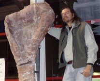 Research team leader Bernardo González Riga stands with the complete right humerus (upper arm bone) of the type specimen of the new titanosaur Notocolossus gonzalezparejasi.