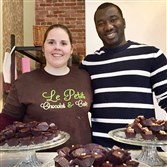 Amanda and Ibrehim Sougouna stand in front of platters of hand-dipped chocolates at their Le Petit Chocolat & Cafe on the South Side.