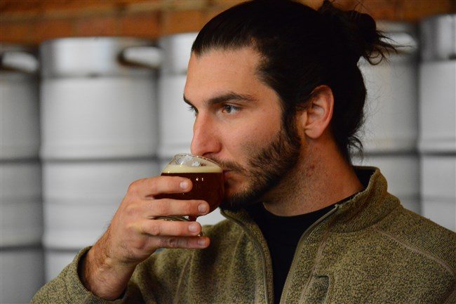 Jake Bier, owner of War Streets Brewery, tastes his beer at the brewery in the North Side.
