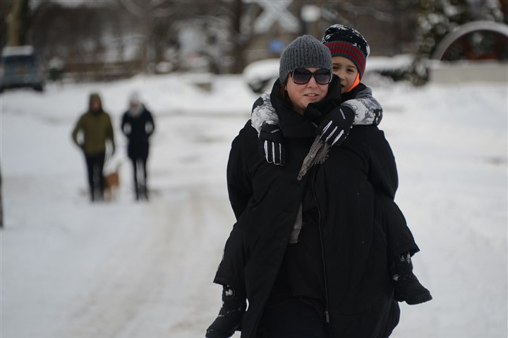 web_snow-jan23_PP Heather Mallak from Lawrenceville carries her son, Zeev, 6, the final way home after a morning of walking along the Riverfront Trail in Lawrenceville Saturday.