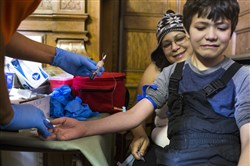 Flint resident Mycal Anderson, 9, reacts to having his blood drawn for lead testing while sitting on his mother Rochelle Anderson's lap at the Flint Masonic Temple on Saturday in Flint, Mich.