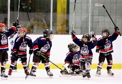 Youth playing in the Mite division (8 and under) of Robert Morris University Island Sports Center's youth hockey league cheer after winning a race at the end of practice.