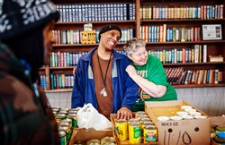 Volunteers Preston Tyson and Mary Kay Coleman laugh between clients at the Focus on Renewal Community Center food pantry in McKees Rocks.