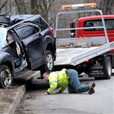 A tow truck operator checks for clearance while removing a wrecked vehicle on Ardmore Boulevard in Forest Hills.