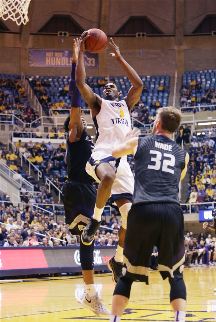 wvu0127 West Virginia forward Jonathan Holton (1) drives the basket while being defended by Kansas State forward Wesley Iwundu (25) in the second half Tuesday night in Morgantown, W.Va. (AP Photo/Raymond Thompson)