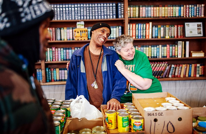 20160127arFocusOnRenewal06-5 Volunteers Preston Tyson and Mary Kay Coleman laugh between clients at the Focus on Renewal Community Center food pantry in McKees Rocks.